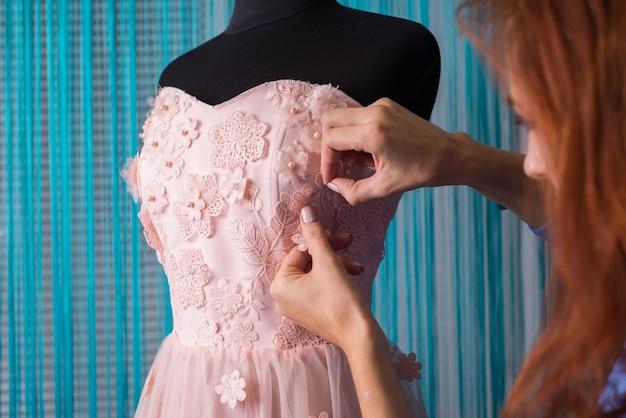 Il processo di creazione dei vestiti. designer professionista, artigiano artigianale, cuce fiori su un vestito rosa, su un manichino, in un laboratorio. sartoria, abito da donna. abito da sposa rosa Foto Premium