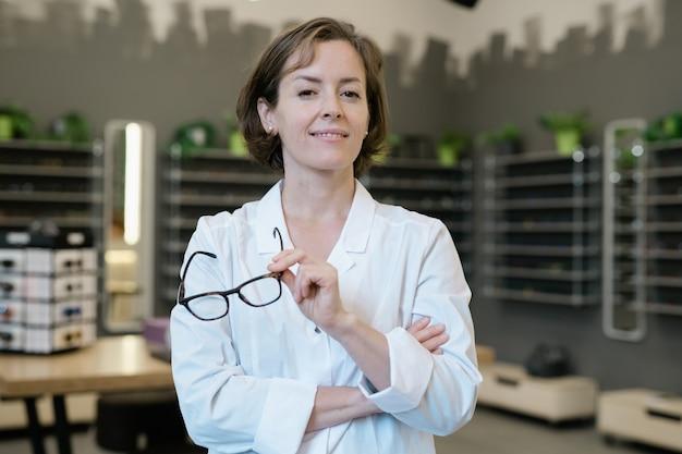 All'ottico optometrista femminile professionale in whitecoat che tiene un paio di occhiali nuovi nell'ambiente del negozio di ottica Foto Premium