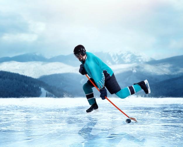 Giocatore professionista di hockey su ghiaccio in esercizio uniforme sul lago ghiacciato, foresta invernale sullo sfondo. pattinaggio sul ghiaccio all'aperto Foto Premium