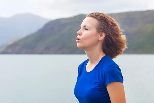 Profilo, ritratto di vista laterale della donna rilassata che respira profondamente aria fresca sul mare, oceano in montagne. calma giovane ragazza capelli rossi zenzero rilassante, meditando all'aperto facendo esercizi di respirazione. copia spazio Foto Premium
