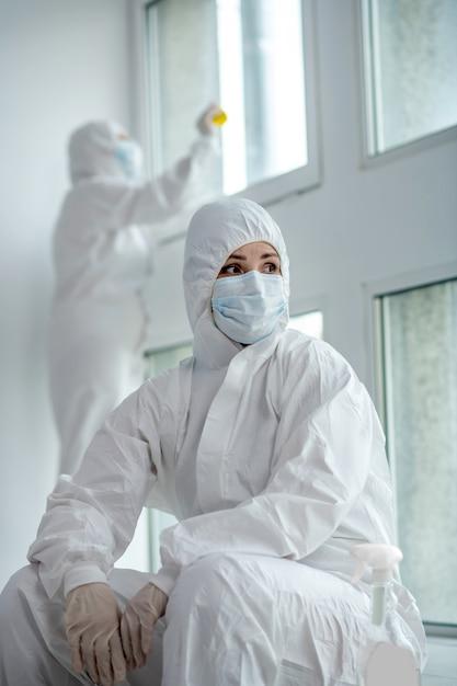 Misure protettive. lavoratore medico biondo stanco in indumenti protettivi e maschera medica che si siedono accanto alla finestra, i suoi vetri disinfezione del suo collega Foto Premium