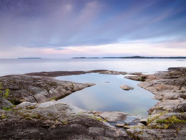 Una pozza d'acqua calma sulla costa rocciosa. lago ladoga. repubblica di carelia, russia Foto Premium