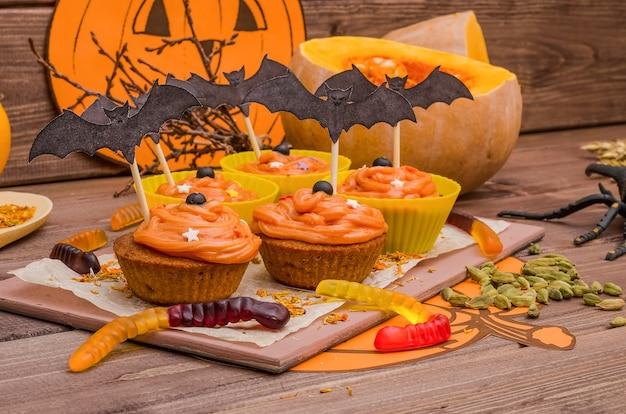 Cupcakes di zucca con crema all'arancia per halloween. idee per la cottura, dolci. Foto Premium