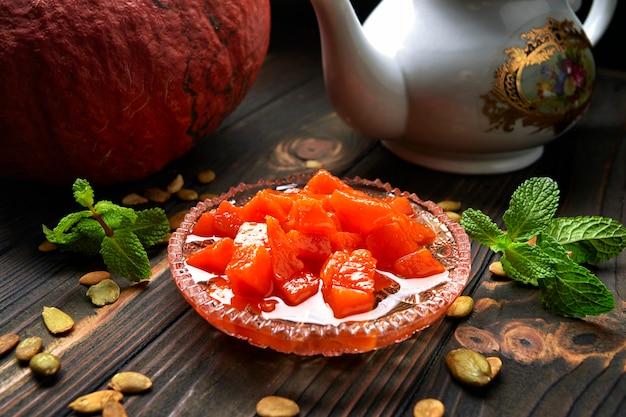 Marmellata di zucca, su un piano di legno scuro, con zucca, menta e semi di zucca Foto Premium