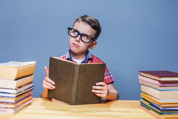 Allievo con gli occhiali che ottiene la conoscenza da un libro di testo Foto Premium