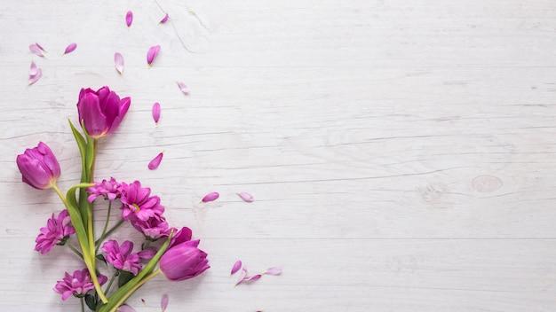 Fiori viola con petali sul tavolo Foto Premium