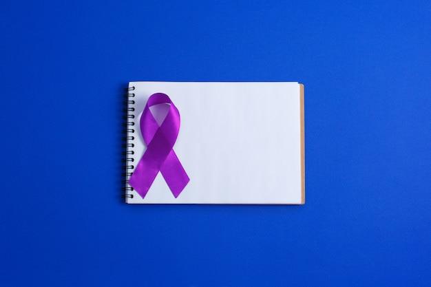 Nastri viola e quaderno aperto, morbo di alzheimer, cancro del pancreas, consapevolezza dell'epilessia, consapevolezza della violenza domestica, Foto Premium