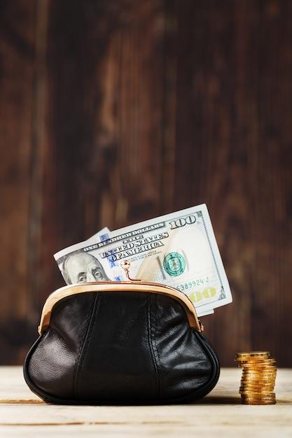 Borsa con soldi e sul tavolo di legno. budget per investimenti in futuro. Foto Premium