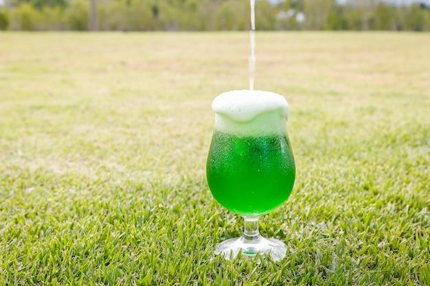 Mettere la birra nel bicchiere per il giorno di san patrizio. sul prato. Foto Premium