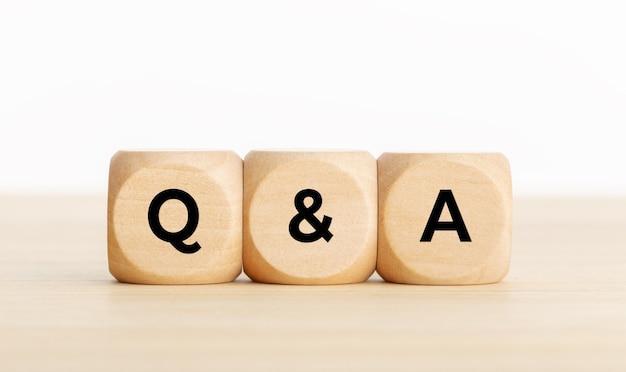 Q&a o domande e risposte concetto. blocchi di legno con testo sulla scrivania. copia spazio Foto Premium