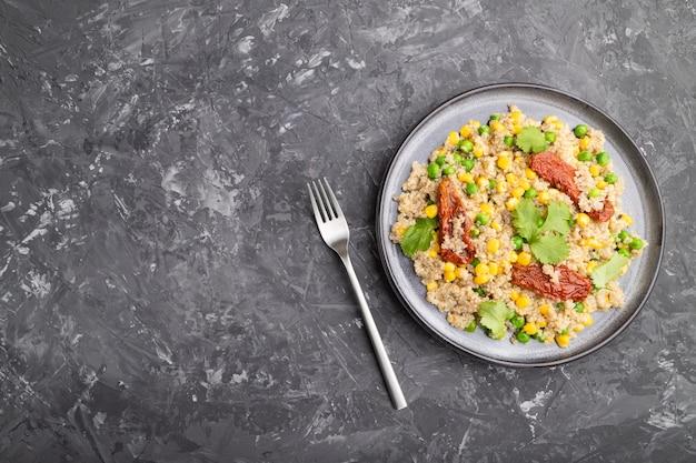 Porridge di quinoa con piselli, mais e pomodori secchi sul piatto di ceramica su un tavolo di cemento grigio. vista dall'alto, piatto laico, copia dello spazio. Foto Premium