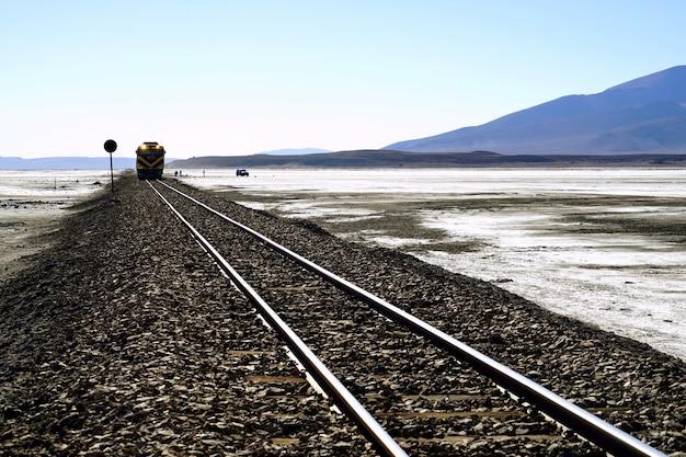 La ferrovia e il treno nel mezzo del deserto. Foto Premium