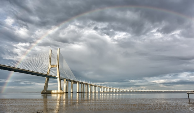 Rainbow sul ponte vasco de gama, lisbona, portogallo Foto Premium