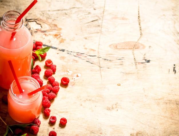 Succo di lampone nella brocca e nei bicchieri. su un tavolo di legno. Foto Premium