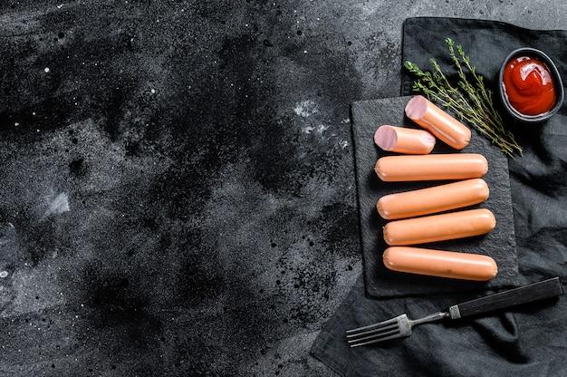 Salsicce classiche di manzo crudo su una tavola di pietra. sfondo nero Foto Premium