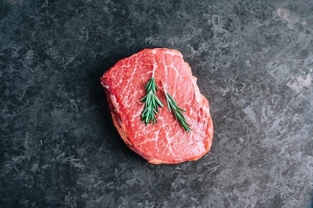 Bistecca di manzo cruda su sfondo nero con rosmarino Foto Premium