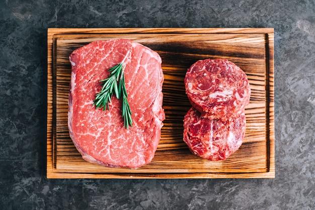 Bistecca di manzo cruda e bistecca tonda tritata per hamburger su tavola di legno Foto Premium