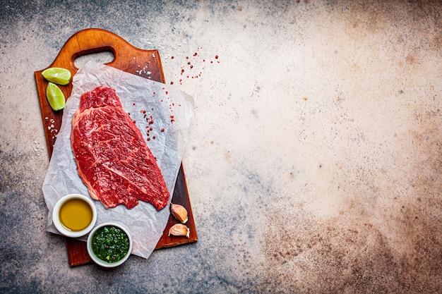 Bistecca di manzo crudo con spezie e salsa chimichurri su tavola di legno, sfondo scuro, copia dello spazio. Foto Premium
