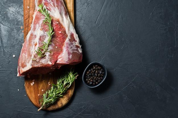 Un cosciotto d'agnello crudo su un tagliere di legno. rosmarino, timo, pepe nero. Foto Premium