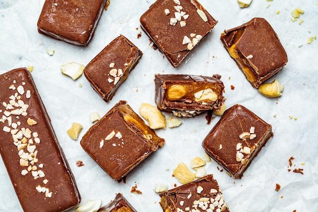 Cioccolato crudo vegano e barrette di caramello, sfondo bianco, vista dall'alto. concetto di dessert sani. Foto Premium