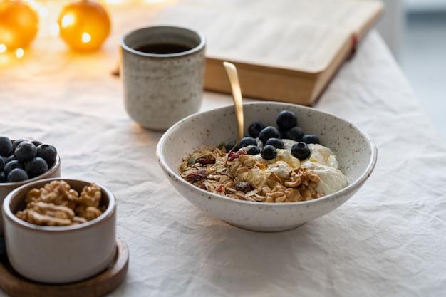 Leggere il libro e mangiare una sana colazione invernale di vacanze di natale con muesli Foto Premium