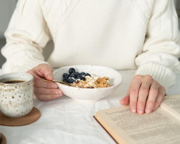 Leggere il libro e mangiare una sana colazione invernale vacanza con muesli muesli e yogurt in una ciotola sul tavolo tavolo bianco. pasto dietetico biologico mattutino con avena Foto Premium