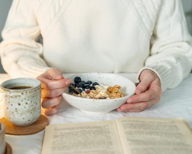 Leggere il libro e mangiare una sana colazione invernale vacanza con muesli Foto Premium