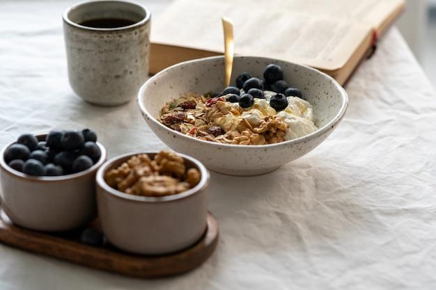 Leggere il libro e mangiare una sana colazione stile di vita con muesli muesli e yogurt in una ciotola sul tavolo bianco, cibo di cereali con semi di noci. pasto dietetico biologico mattutino con avena Foto Premium