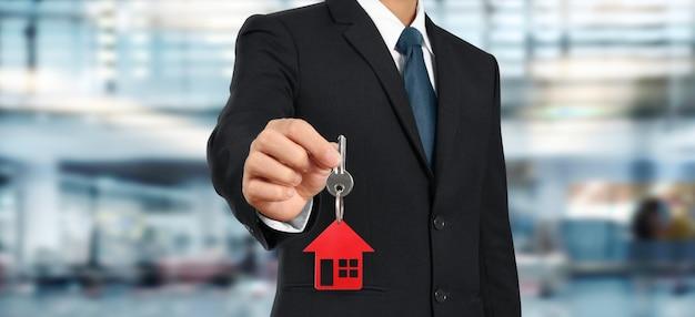 Agente immobiliare che consegna le chiavi di casa in mano Foto Premium