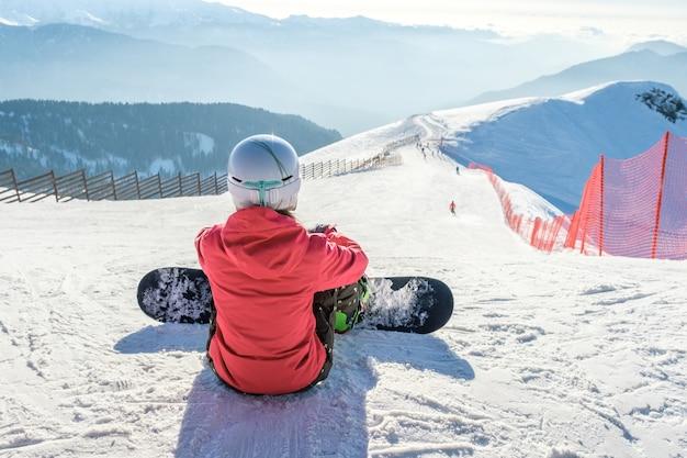 Vista posteriore dello snowboarder in abbigliamento sportivo con attrezzatura che riposa in cima alla pista da sci che gode della vista Foto Premium