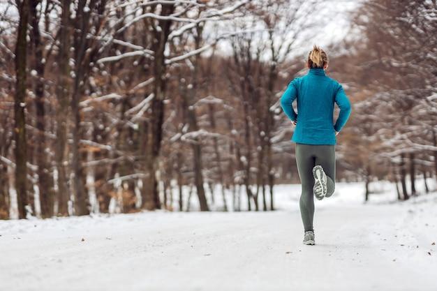 Vista posteriore della sportiva fare jogging in natura in caso di neve. Foto Premium