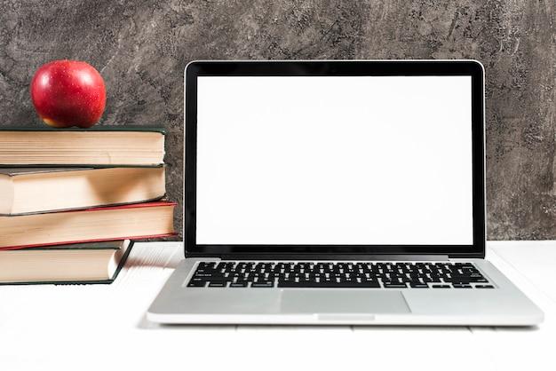 Mela rossa sul impilati di libri vicino al computer portatile sullo scrittorio bianco contro il muro di cemento Foto Premium