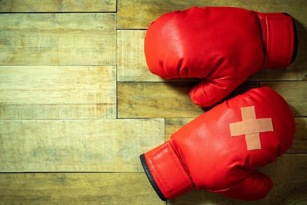 Guantoni da pugile rossi disposti sul pavimento di legno in palestra Foto Premium