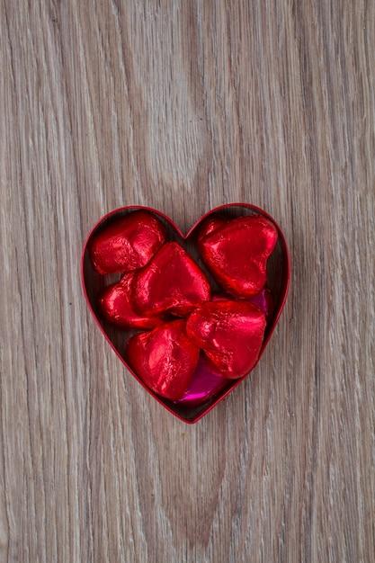Caramelle rosse nel cuore sulla tavola di legno Foto Premium