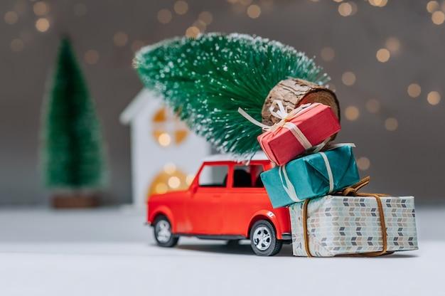 Macchina rossa con un albero di natale sul tetto. sullo sfondo della casa. concetto sul tema del natale e del nuovo anno. Foto Premium
