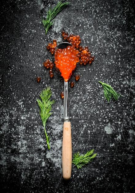 Caviale rosso in un cucchiaio con aneto. su sfondo nero rustico Foto Premium