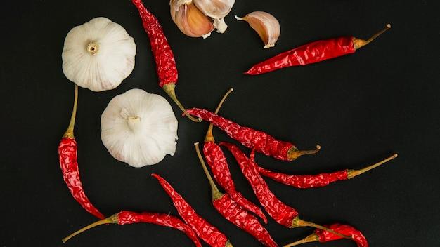 Peperoncino rosso e aglio su sfondo nero Foto Premium