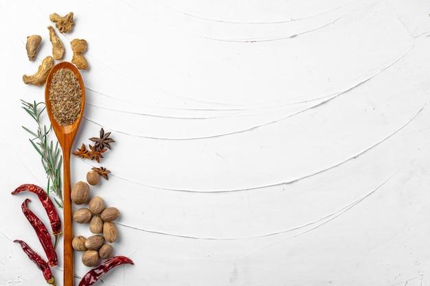Peperoncini rossi e altre spezie su fondo strutturato bianco, vista superiore Foto Premium