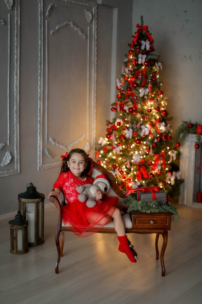 Foto rossa di natale della bambina sul sofà con un regalo in sue mani. Foto Premium