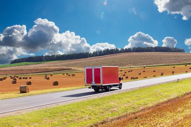 Pista di consegna rossa, furgone sull'autostrada, sullo sfondo di un campo di grano raccolto giallo. c'è un posto per la pubblicità Foto Premium