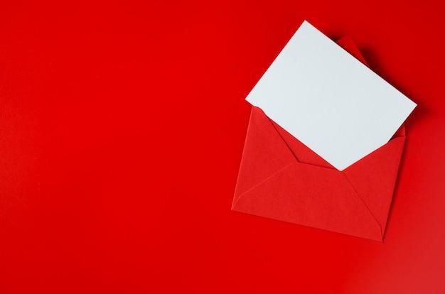 Busta rossa con carta bianca vuota. san valentino sullo sfondo. mockup di lettera d'amore. Foto Premium
