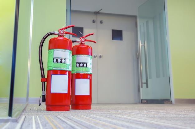 Serbatoio rosso degli estintori alla porta di uscita nell'edificio Foto Premium