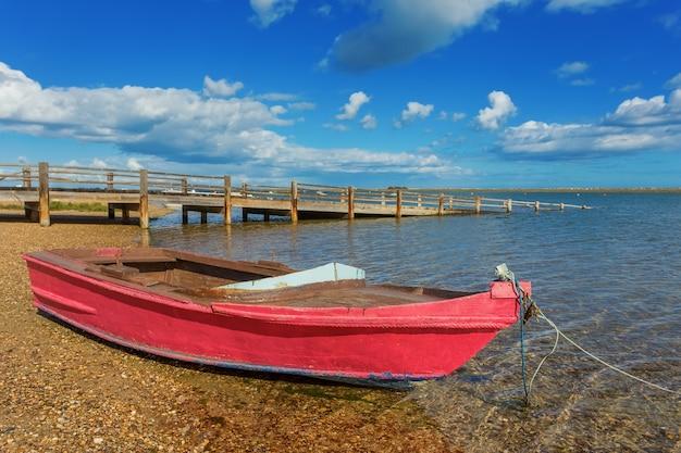 Peschereccio rosso sulla riva. vicino al ponte Foto Premium