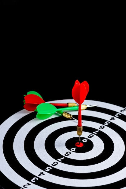 Freccia rossa e verde freccia che colpisce il centro bersaglio freccette isolati su sfondo nero, Foto Premium