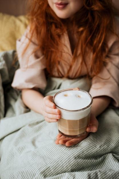 Ragazza dai capelli rossi a letto con una tazza di caffè con schiuma di latte. Foto Premium
