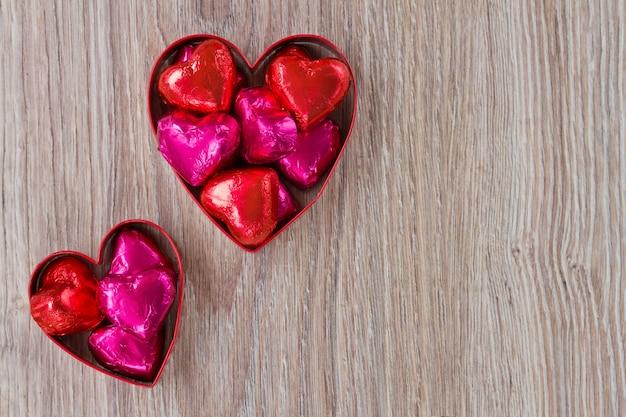 Caramelle rosse e rosa del cuore sulla tavola di legno Foto Premium