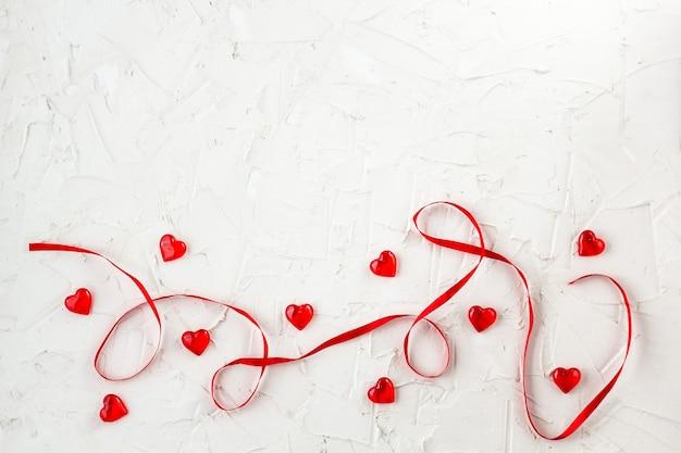 Nastro rosso con cuori. per progettare biglietti e auguri per san valentino. vista dall'alto con copia spazio Foto Premium