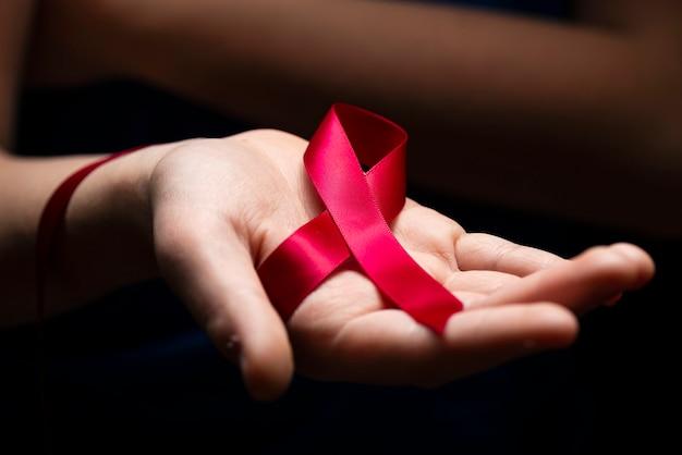 Nastro rosso nelle mani della donna su sfondo scuro per il concetto di giornata mondiale contro l'aids. Foto Premium