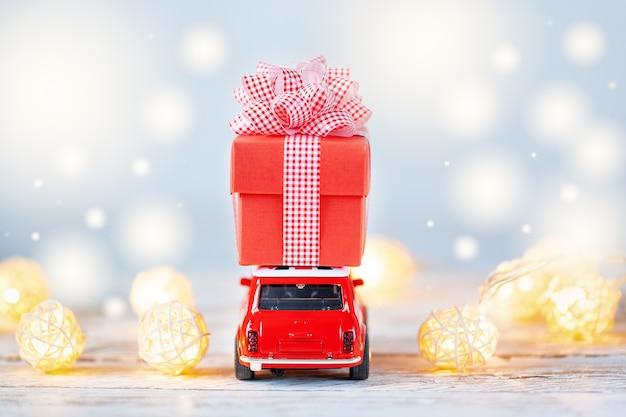 Automobile rossa del giocattolo che porta sul tetto una confezione regalo rossa su sfondo blu Foto Premium