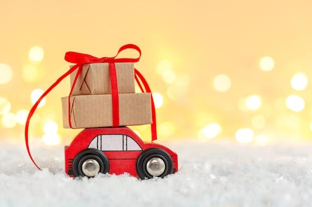 Automobile rossa del giocattolo con la pila di contenitori di regalo di natale Foto Premium